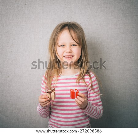 Little beautiful smiling girl with a gift in their hands. - stock photo