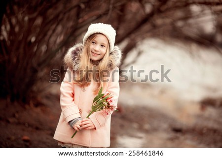 little beautiful smiling girl with long blond hair in the hat and pink coat standing in the park and holding pink spring flowers in her hands  - stock photo