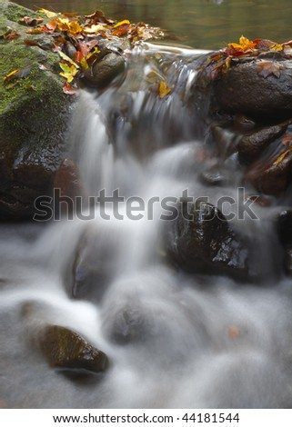 Little beautiful waterfall in the forest at autumn - stock photo