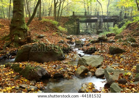 Little beautiful waterfall in the forest at autumn with bridge - stock photo