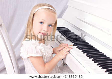 little beauty blond girl in white beautiful dress  sitting at white piano, looking at camera  - stock photo