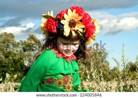 little beauty in the national Ukrainian costume on the background of a sky - stock photo