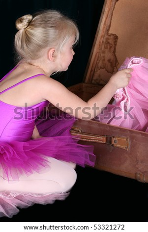 Little blond ballerina looking for a costume in an antique suitcase - stock photo