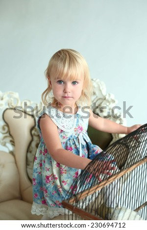 little blond beautiful girl beside the cage with parrot - stock photo