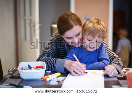Little blond boy and his mother making together preschool homework