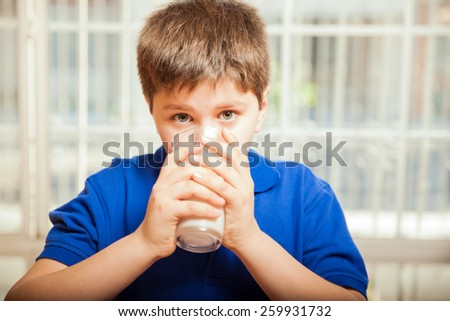 Little blond boy drinking a whole glass of milk at home for breakfast - stock photo