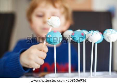 Little blond boy eating colorful cake pops, indoors. Selective focus on cake pops. - stock photo