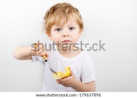 Little blond boy of two years eating cheesecake muffin. - stock photo
