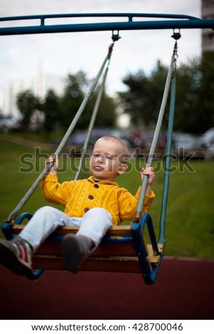 Little blond boy playing on a swing outdoor, selective focus