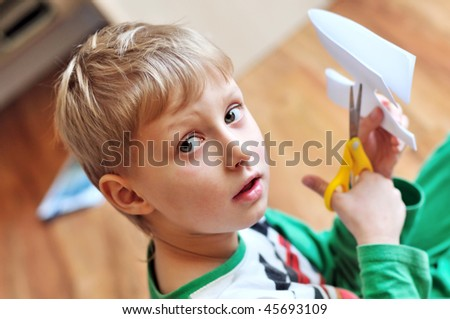 little blond boy scissoring paper and looking at the camera