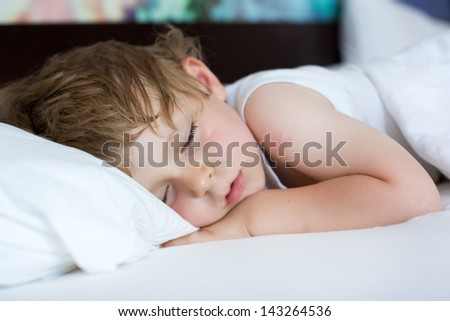 Little blond boy sleeping in his bed