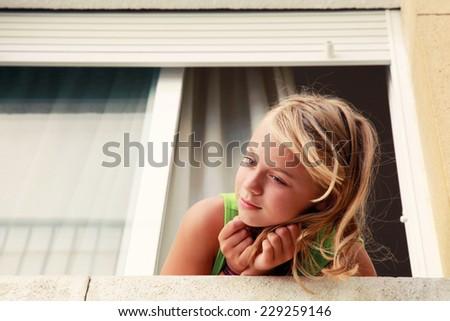 Little blond Caucasian girl in the window, outdoor portrait, retro toned Instagram filter effect - stock photo