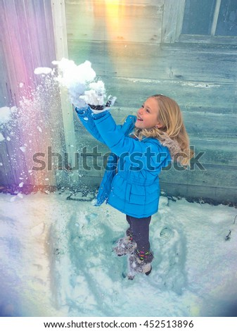little blond Caucasian girl tossing snow in rainbow by old cabin - stock photo