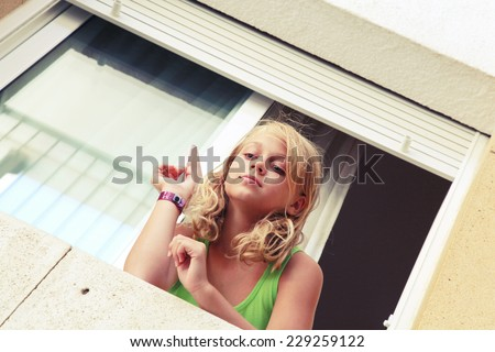 Little blond Caucasian girl with paper plane in the window, outdoor closeup portrait, retro toned Instagram filter effect - stock photo