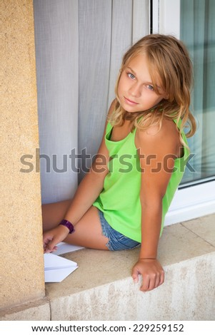 Little blond Caucasian girl with paper plane in the window, outdoor vertical portrait