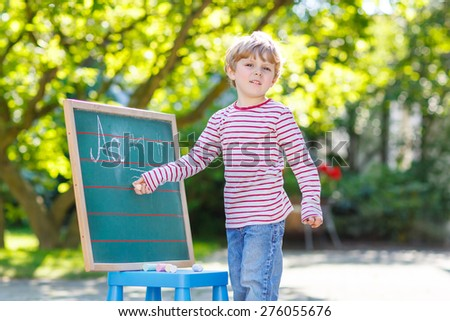 Little blond child at blackboard practicing writing letters and mathematics, outdoor school or nursery. Kid learning and schoolboy concept. On summer sunny day. Back to school.