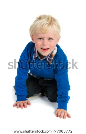 Little blond child is playing at the floor