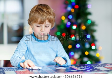 Little blond child playing with cars and toys at home, indoor. funny boy having fun with gifts. Colorful christmas lights on background. Family, holiday, kids lifestyle concept. - stock photo
