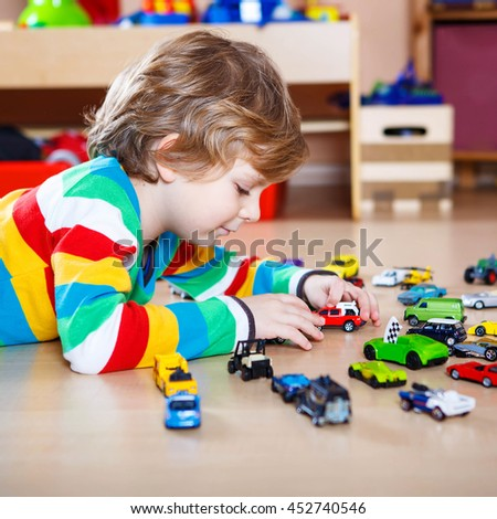 Little blond child playing with lots of toy cars indoor. Kid boy wearing colorful shirt. Happy preschool child having fun at home or nursery. - stock photo