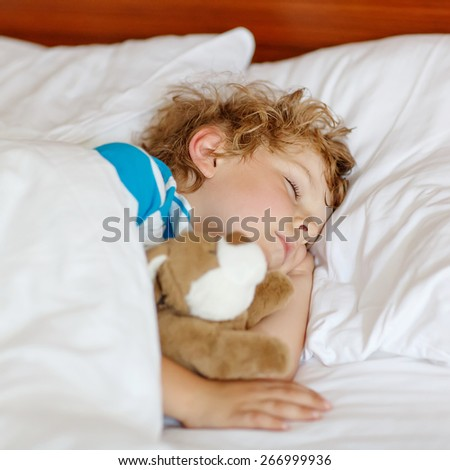 Little blond child sleeping in his bed with toy - stock photo