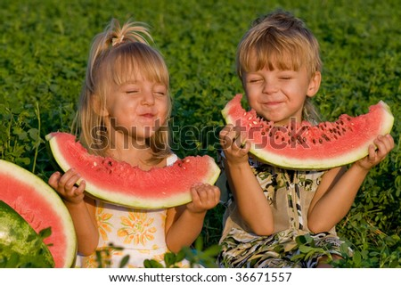 Little blond girl and boy with a piece of watermelon in hands - stock photo