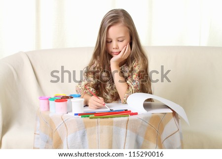 Little blond girl drawing at home on sofa - stock photo