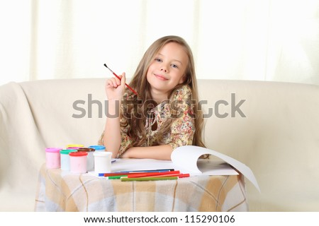 Little blond girl drawing at home on sofa and looking above - stock photo