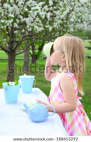 Little blond girl having a garden tea party - stock photo
