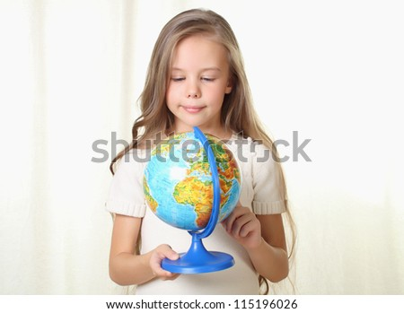 Little blond girl holding and looking on globe - stock photo