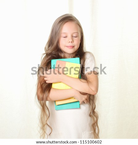 Little blond girl holding different books and dreaming with closed eyes - stock photo