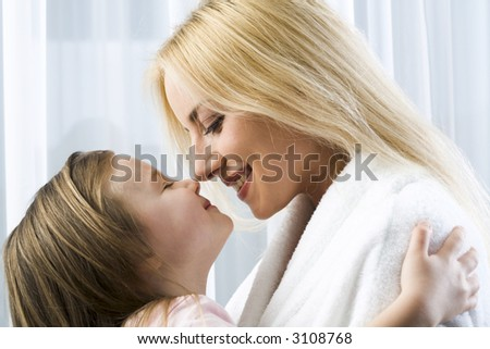Little blond girl hugging her smiling mother reaching to kiss her - stock photo