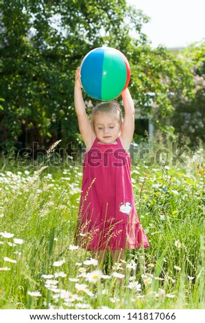 Little blond girl in a red summer dress is playing with a beach ball on a meadow full of blooming daisies - stock photo