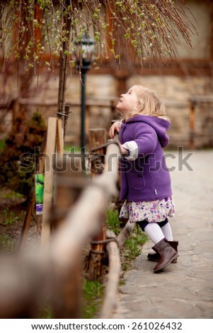 little blond girl in purple coat and dress is walking in the park near the wooden fence - stock photo
