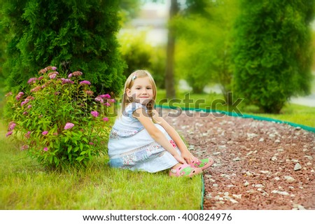 Little blond girl in white dress sitting on green grass in blossom garden enjoy summer vacation in country side