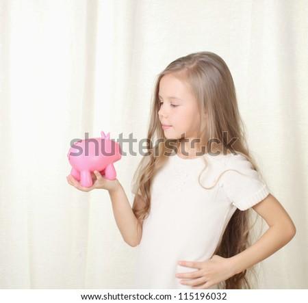 Little blond girl looking on piggy moneybox - stock photo