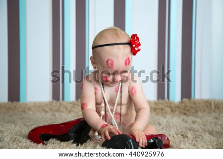 Little blond girl playing with bead and red shoes - stock photo