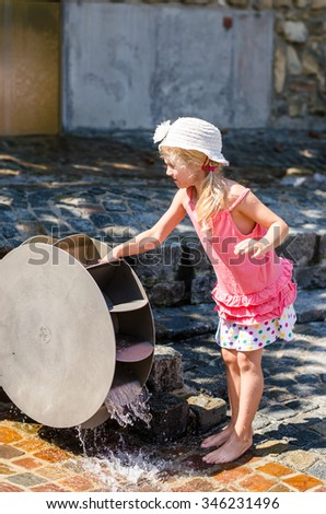 little blond girl playing with wooden water mill attraction  - stock photo
