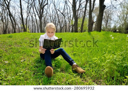 little blond girl reading book between green spikes meadow garden - stock photo