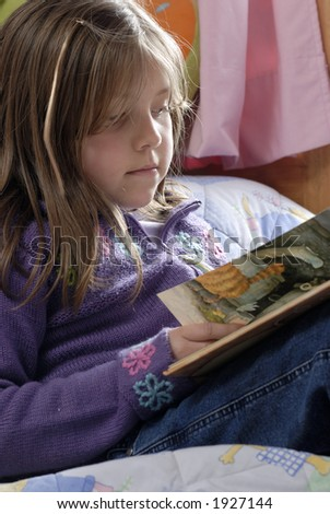 little blond girl reading over a bed - stock photo