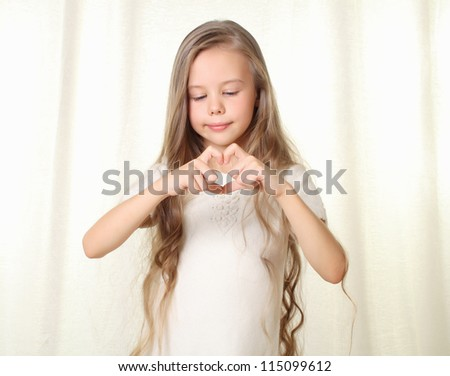 Little blond girl shows heart sign made by fingers - stock photo