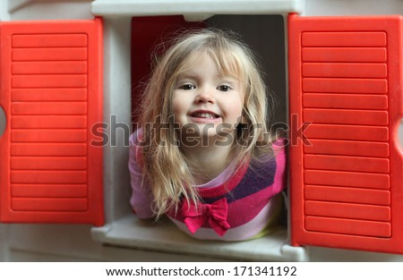 Little blond girl smiling through the window of kids playhouse - stock photo