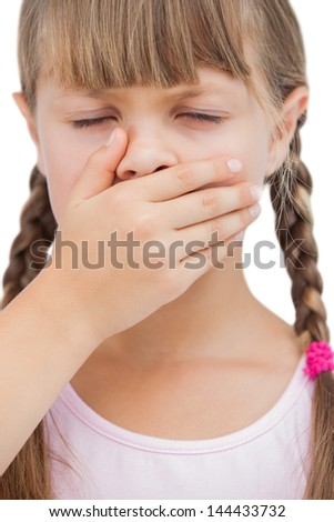 Little blond girl with her hand on her mouth with her eyes closed on white background
