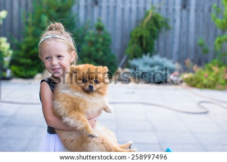Little blond girl with her pet dog outdoors in park