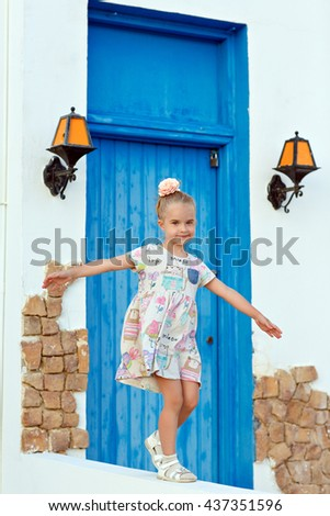 Little blond girl 5 years old walking on the curb as a gymnast in the summer on a background of blue door - stock photo
