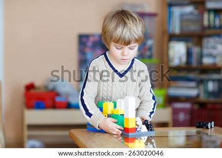 Little blond kid boy playing with lots of colorful plastic blocks indoor. Child having fun with building and creating. - stock photo
