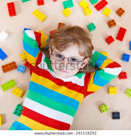 Little blond kid boy playing with lots of colorful plastic blocks indoor. child wearing colorful shirt and glasses, having fun with building and creating.