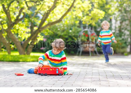 Little blond kid boy playing with red wooden toy bus in summer garden, outdoors. Another boy on background - stock photo