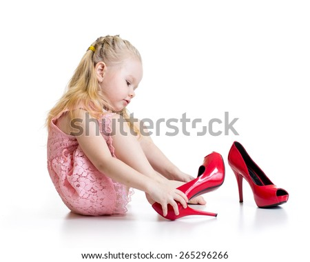 Little blond Kid girl trying big mother shoes on - stock photo