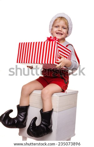 Little blond kid in red costume of dwarf holding big gift box with ribbon. Christmas concept. Studio portrait isolated over white background  - stock photo