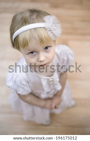 little blond kindergarten girl in princess dress looking up seriously  - stock photo